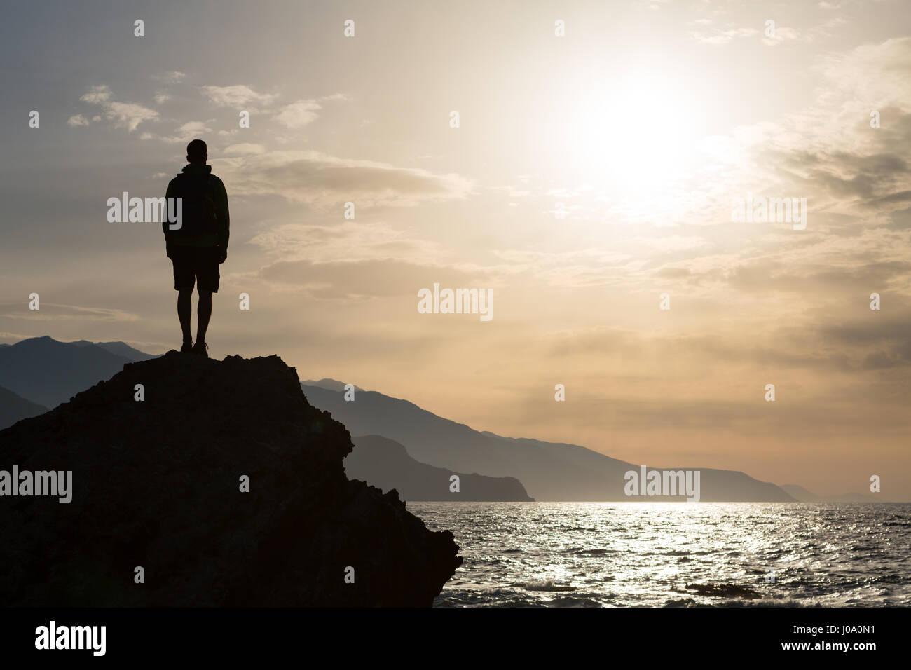 Wanderer oder Läufer Silhouette Backpacker, Mann, Blick auf inspirierende Ozean Landschaft und Inseln auf Berggipfel. Stockbild