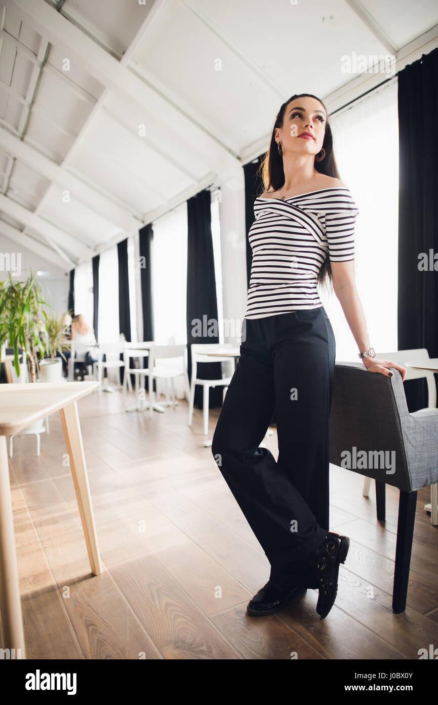 Porträt von schöne junge Frau in einem Café auf Stuhl gelehnt und suchen Sie lächelnd. Erfolgreiche Stockbild
