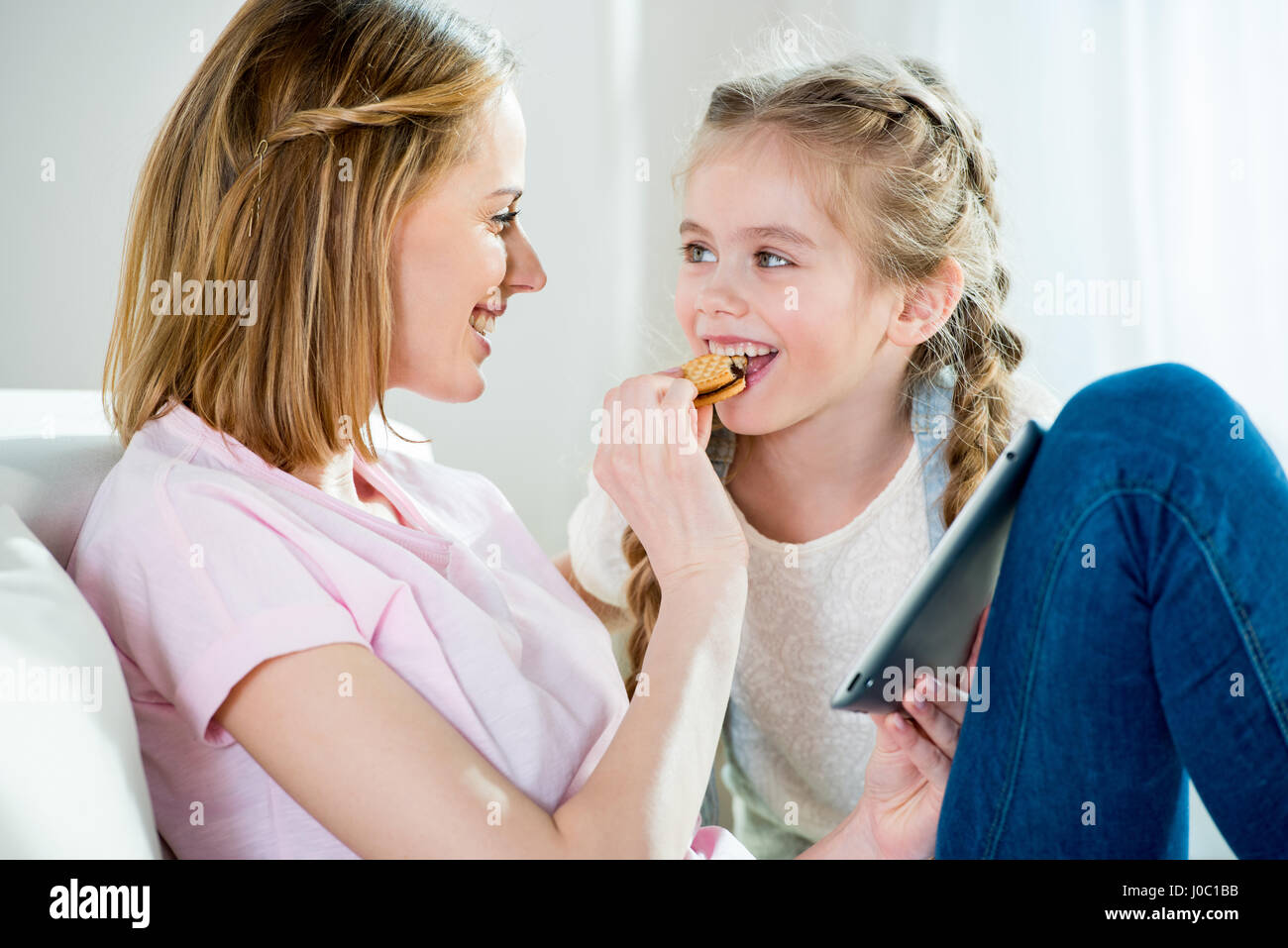 Glückliche Mutter Tochter mit Cookie zu füttern, während der Verwendung von digital-Tablette Stockbild