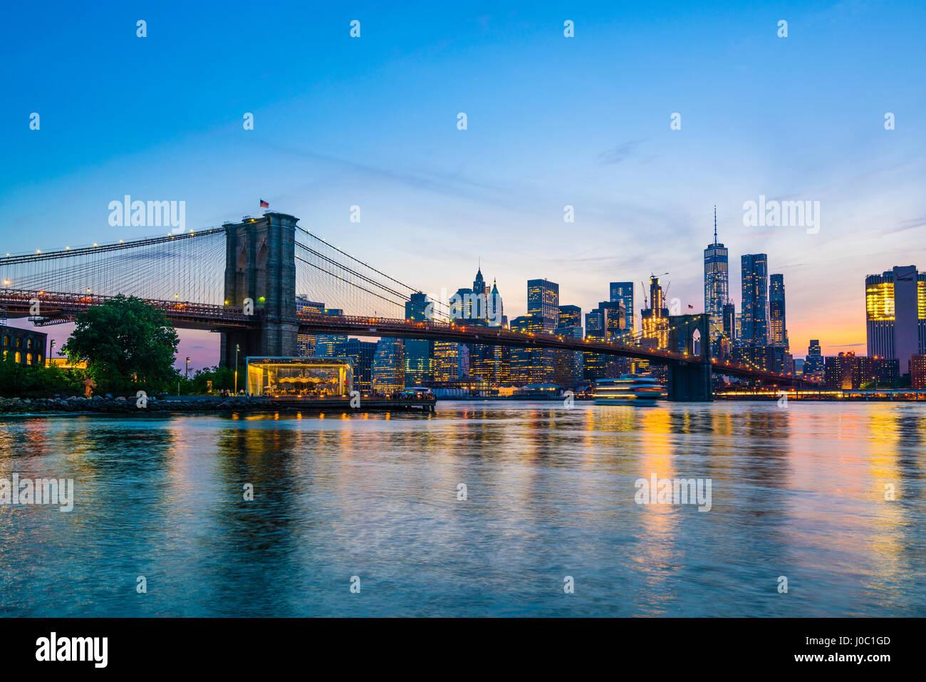 Brooklyn Bridge und Manhattan Skyline in der Abenddämmerung, angesehen vom East River, New York City, USA Stockbild