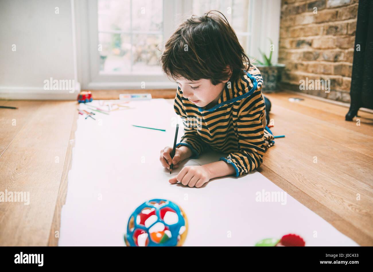 Junge auf Boden auf lange Papier zeichnen Stockbild