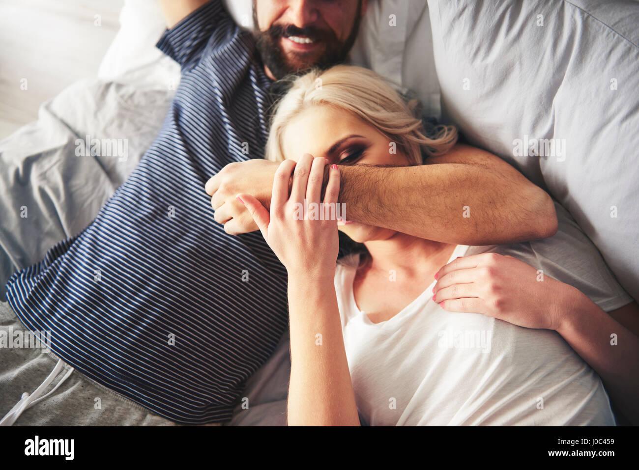 Paar, entspannend auf Bett, herumalbern Stockbild