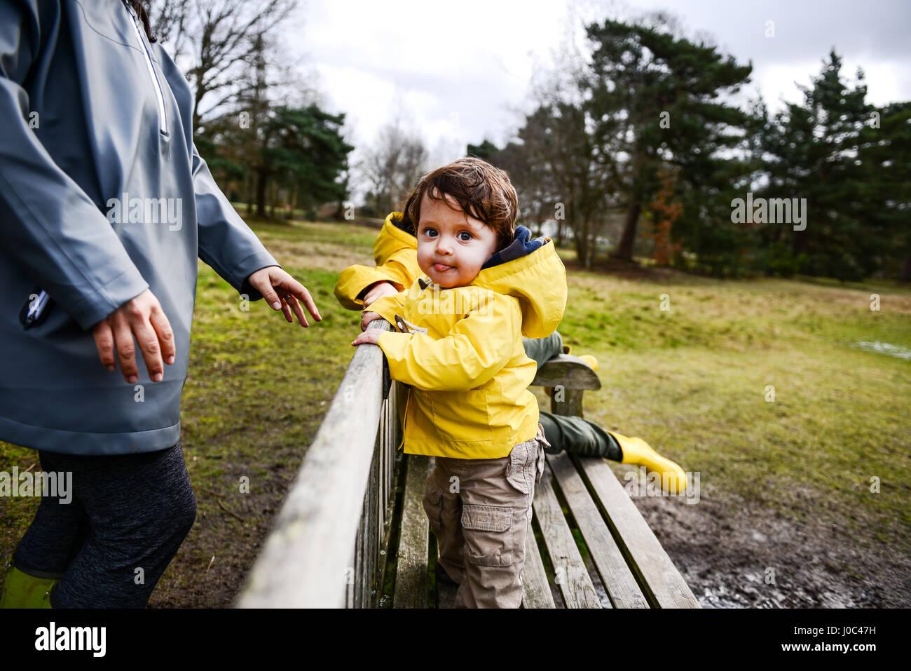 Baby Junge mit Mutter im gelben Anorak auf Parkbank Stockbild