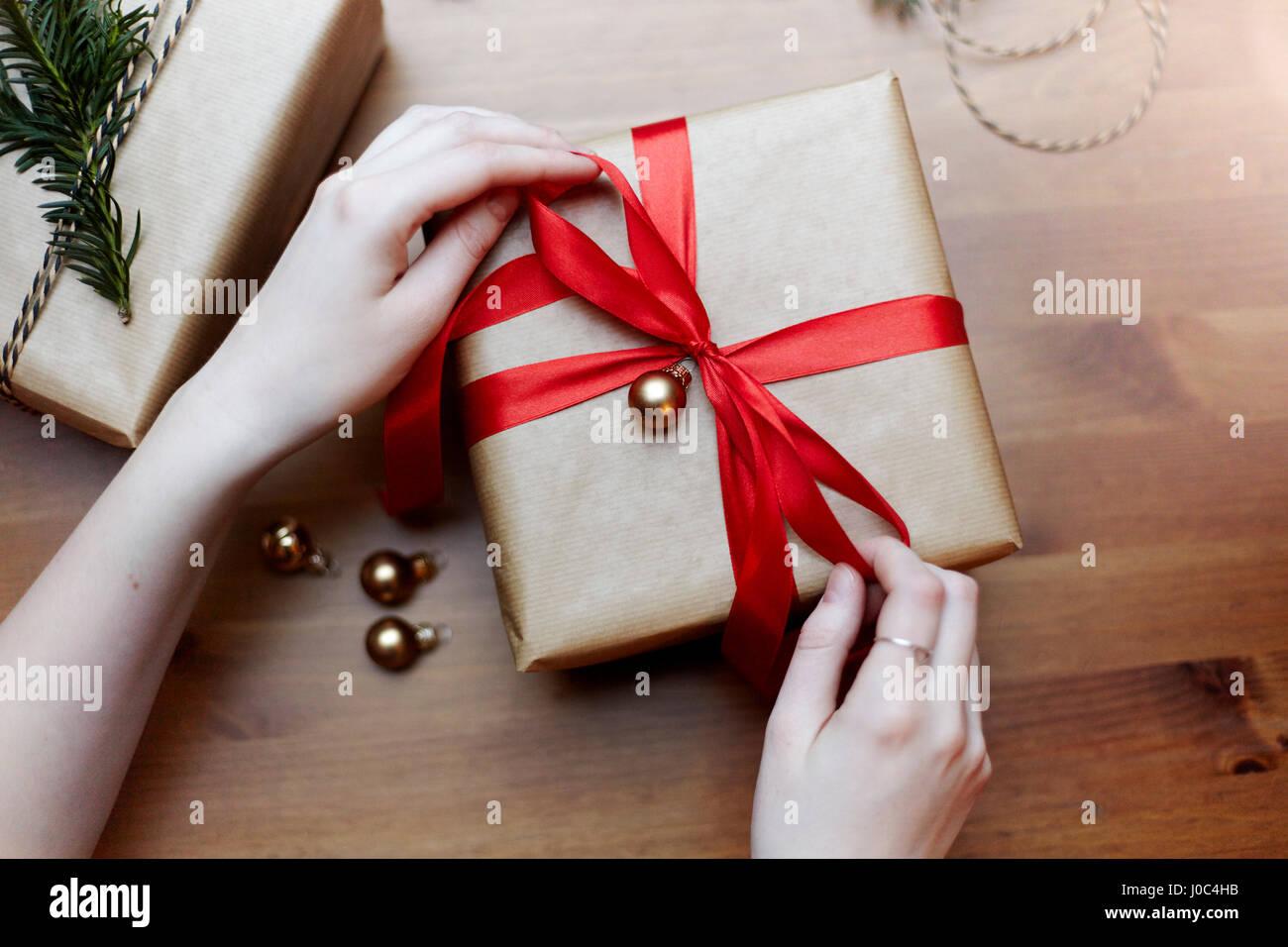 Frau binden roten Schleife auf Weihnachtsgeschenk, Draufsicht ...