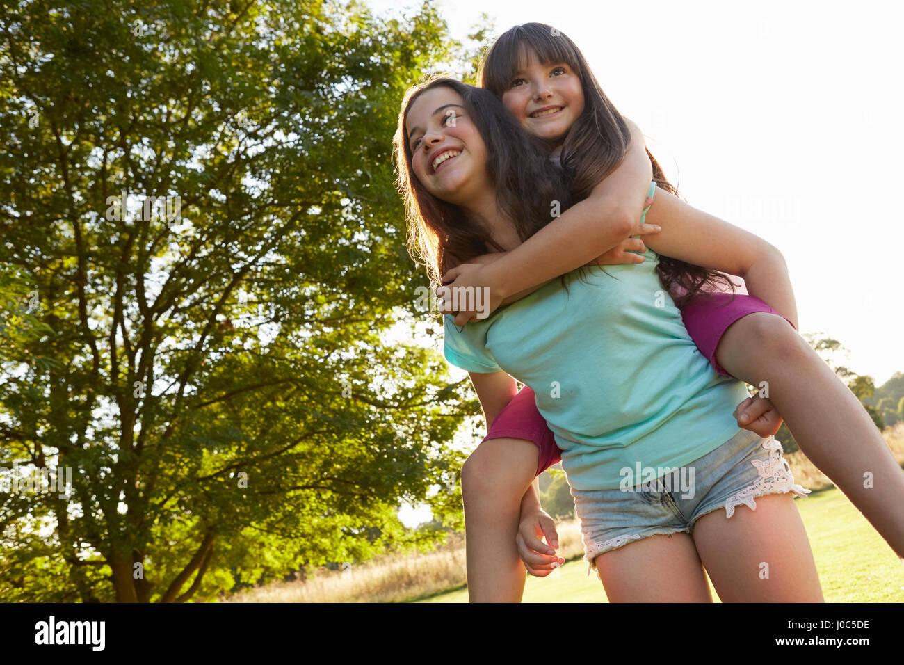 Mädchen, das ihre beste Freundin eine Huckepack im park Stockbild