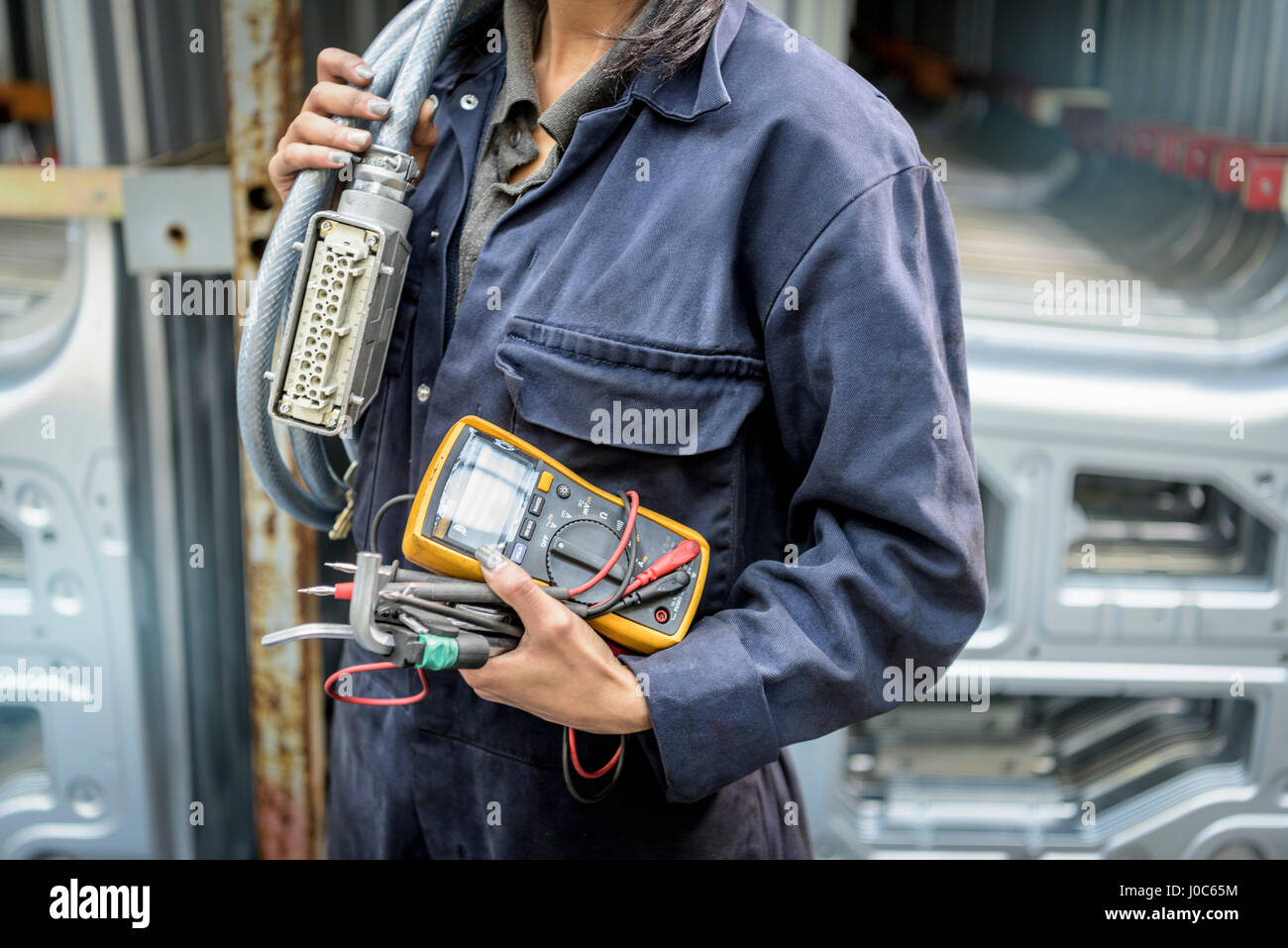 Weiblichen Lehrling Elektriker Holding Ausrüstung in Automobilfabrik, Nahaufnahme Stockbild