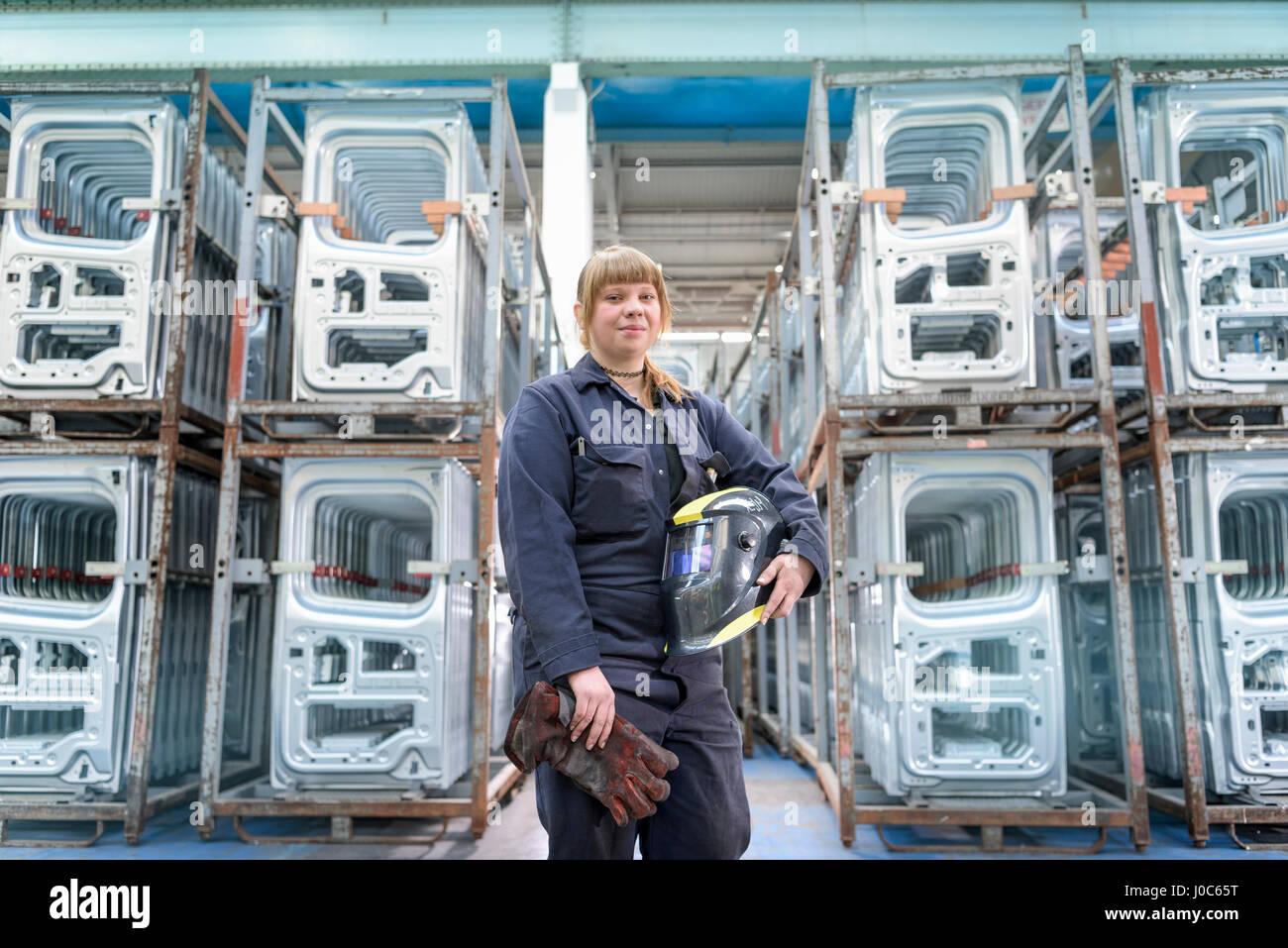 Weiblichen Lehrling Schweißer mit Ausrüstung in Autofabrik, Porträt Stockbild