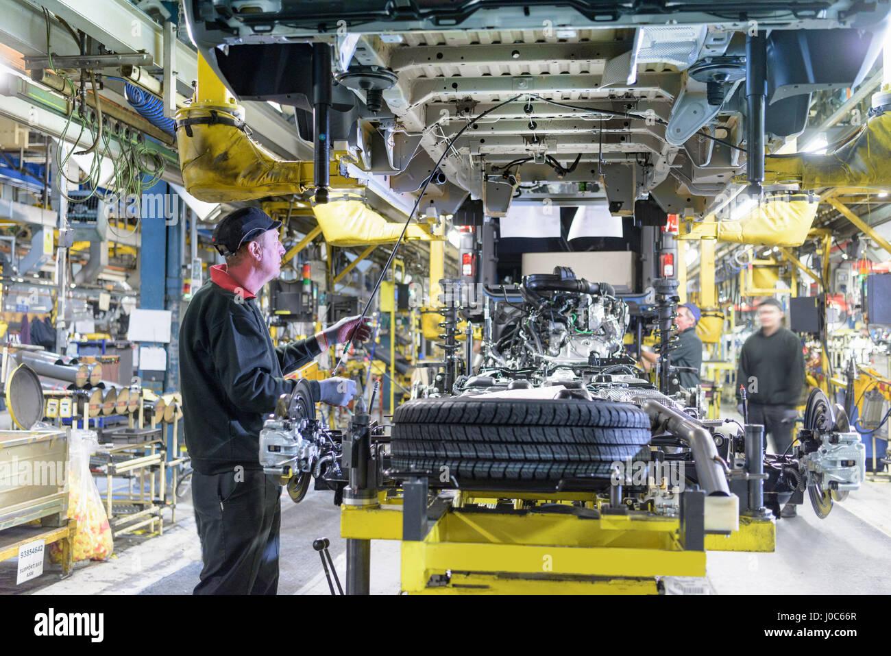 Arbeiter am Fließband in Automobilfabrik Stockbild