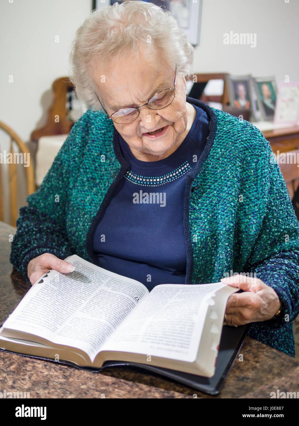 Eine Frau, eine Bibel zu lesen. Eine ältere Senioren liest und blättert in einer großen gedruckten Stockbild