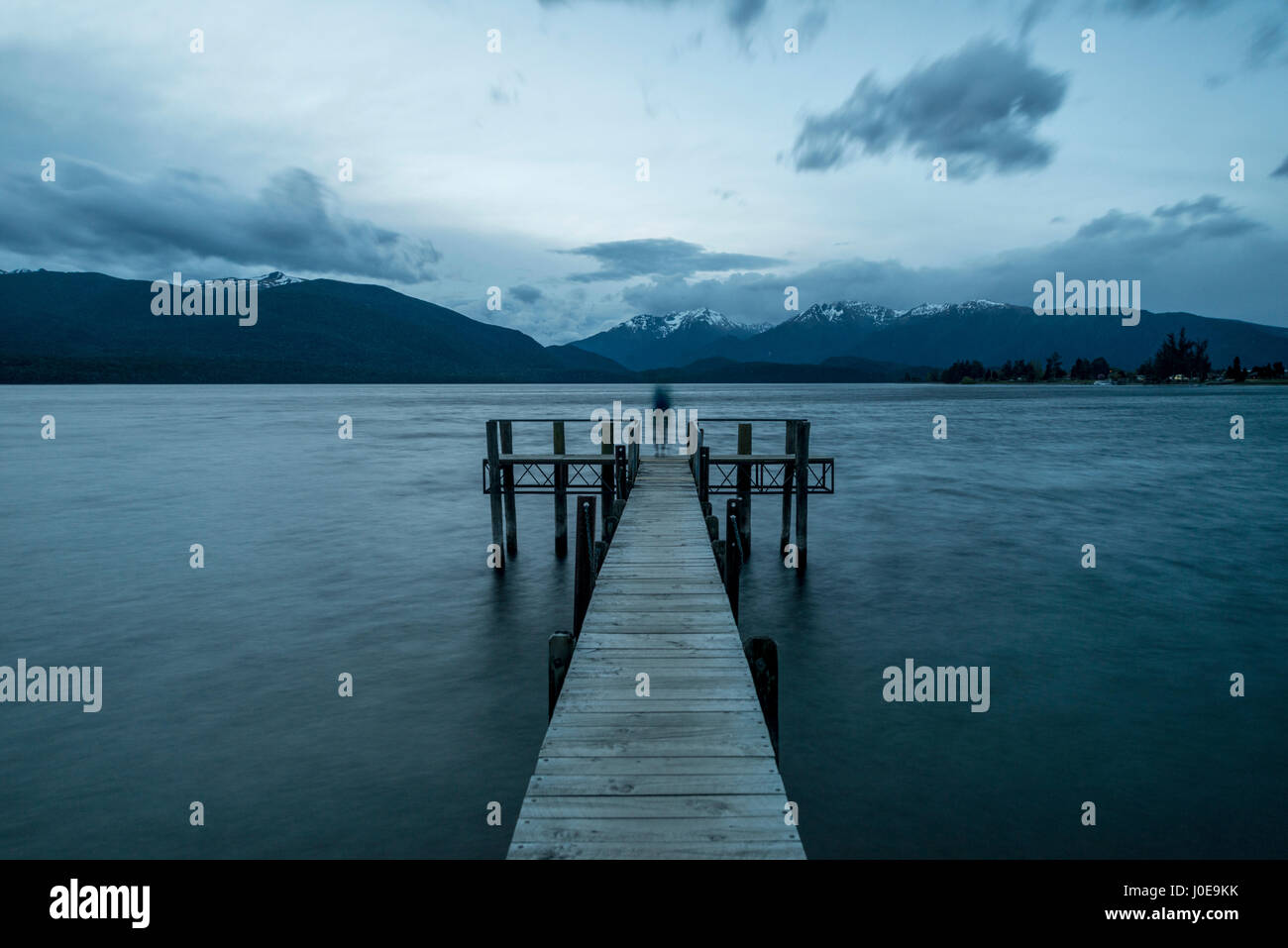 Bewölkter Himmel über Berge, Silhouette stehend auf Dock, Lake Te Anau, Southland, Neuseeland Stockbild