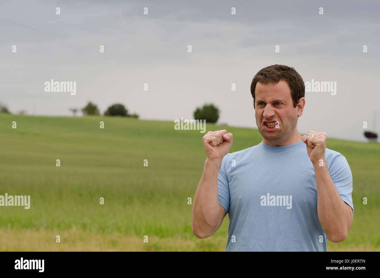 Wütender Mann mit geballten Fäusten draußen auf dem Lande. Stockfoto