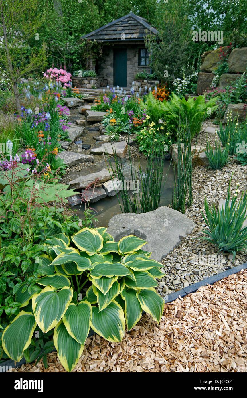Cottage garten pflanzen  Ein Land-Cottage-Garten in einer bewaldeten Steingarten mit bunten ...