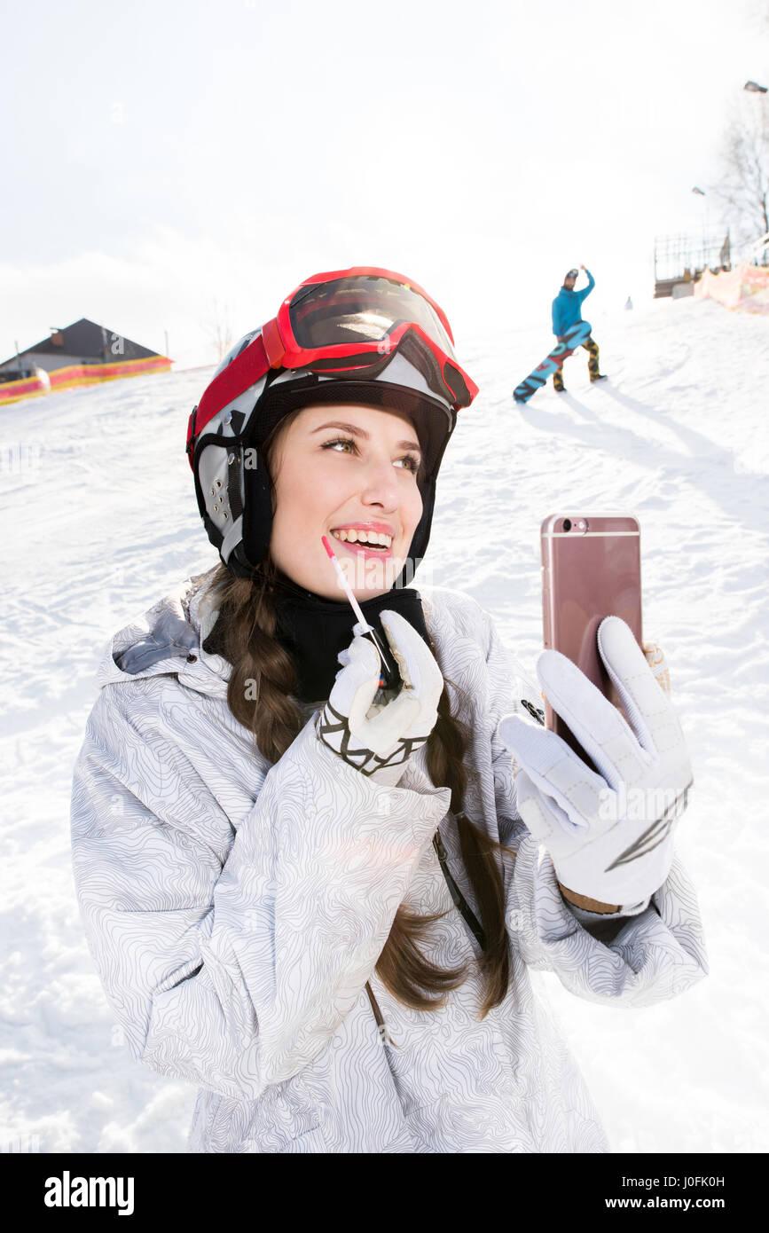 Lächelnden jungen weiblichen Snowboarder Anwendung Lipgloss Smartphone mit gedrückter Stockbild