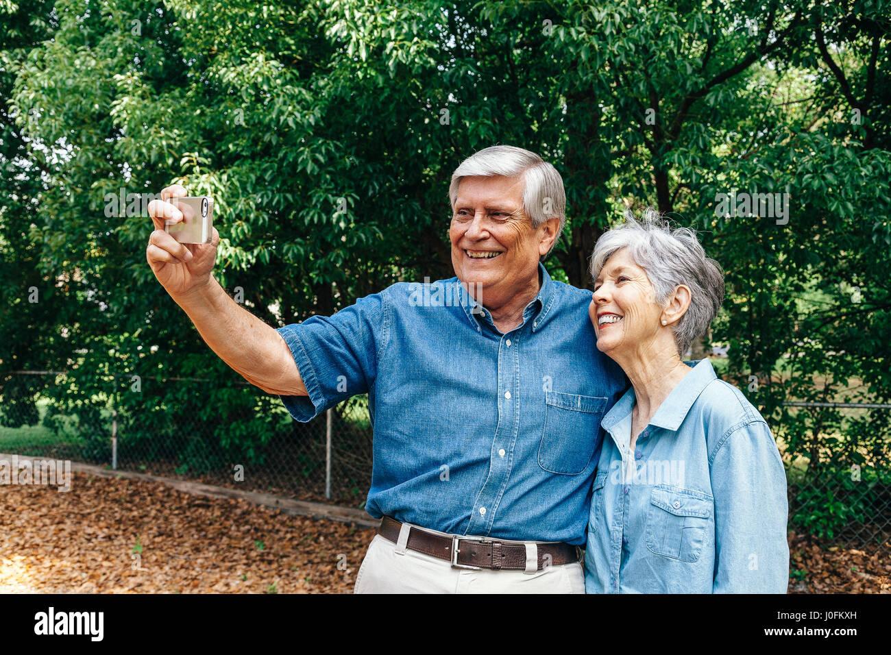 Älteres paar nehmen Selfie im Park Stockbild