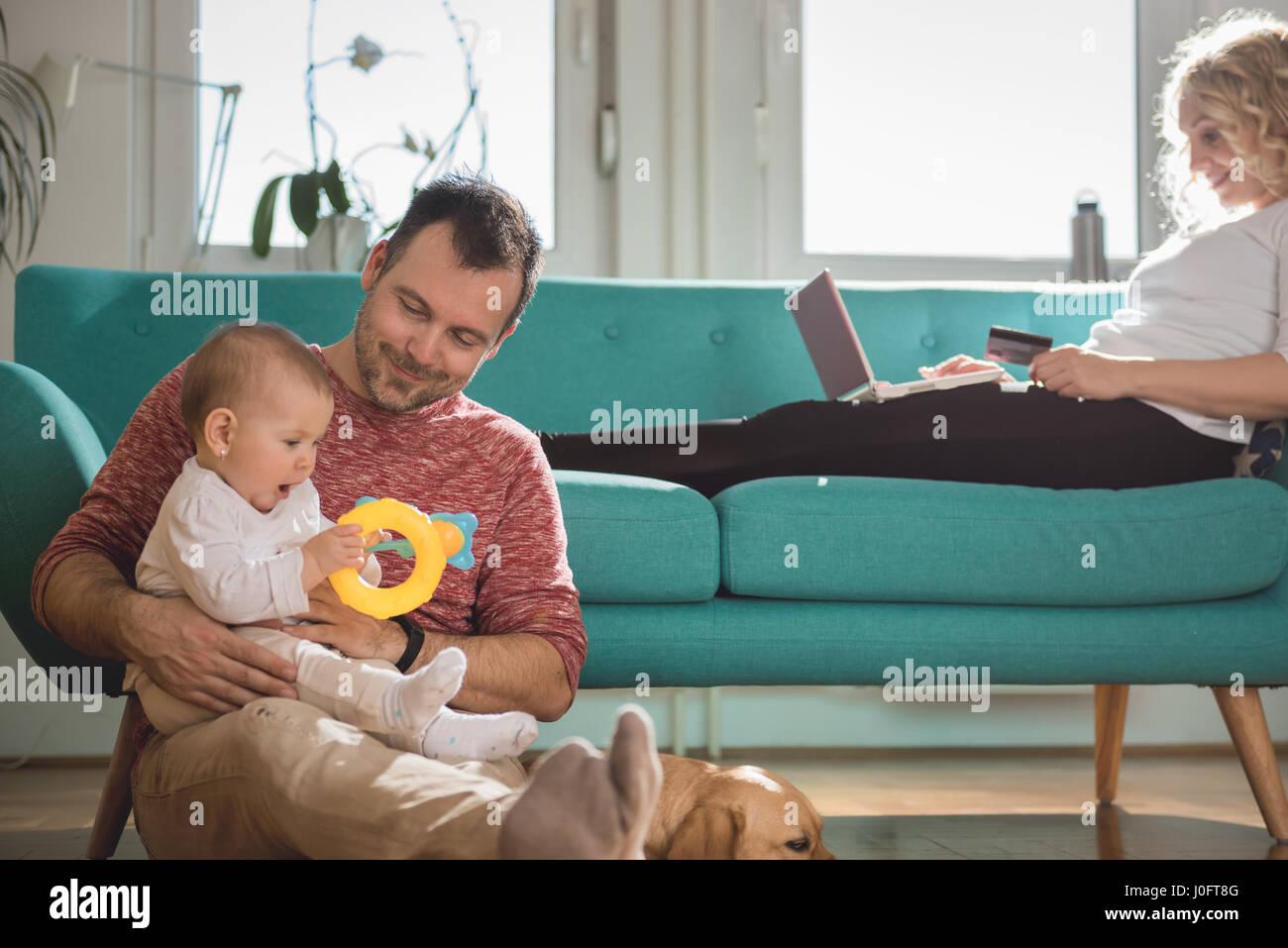 Vater auf dem Boden sitzend und hält Baby im Arm während Frau auf Sofa sitzen und tun, Online-shopping Stockbild