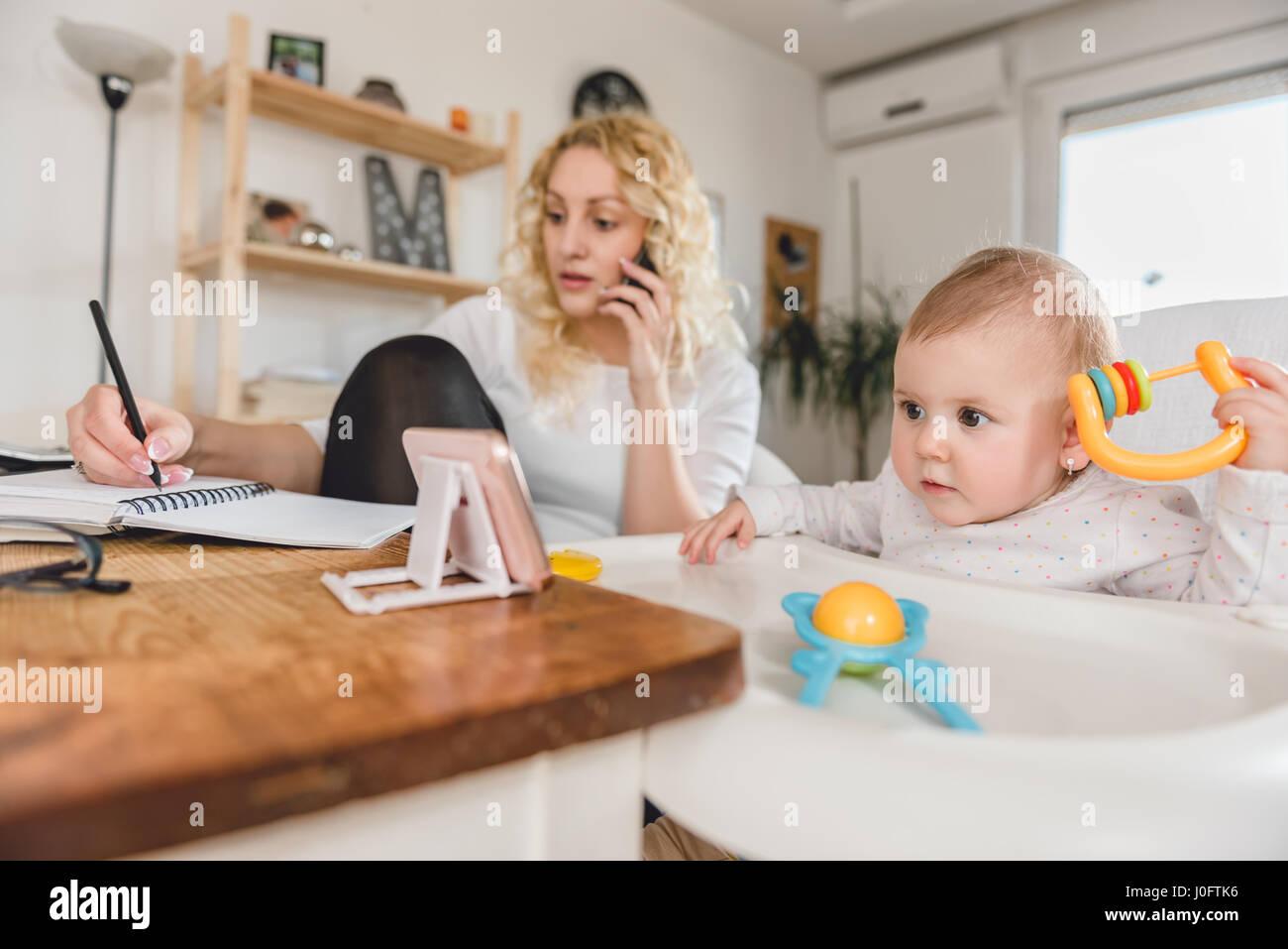 Aufgeregt Baby beobachten Smartphone während Mutter am Smartphone sprechen und schreiben, Notizen zu Hause Stockbild