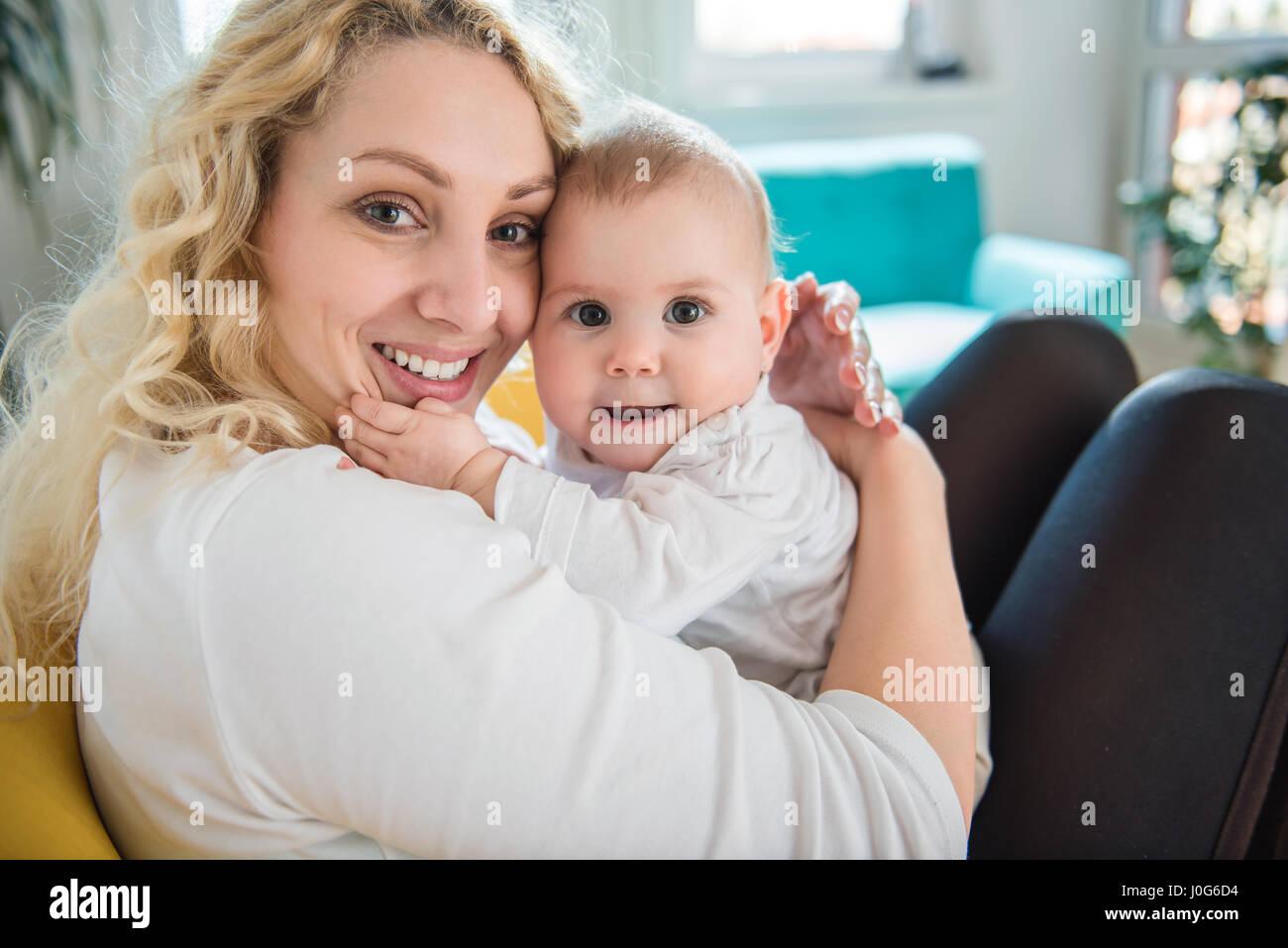 Mutter Baby im Arm halten und sitzen am gelben Sessel Stockbild