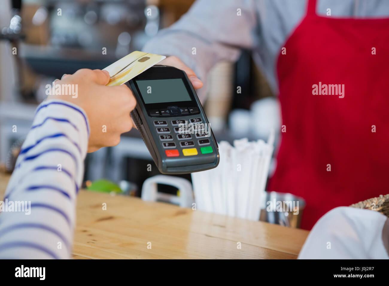 Frau, die die Zahlung durch Kreditkarte am Schalter im CafÃ?© Stockbild