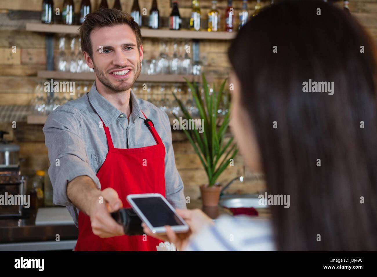 Frau, die die Zahlung durch NFC-Technologie auf dem Handy in Cafà© Stockfoto