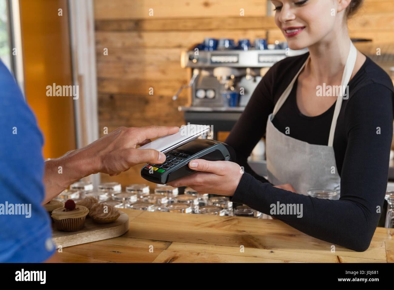 Nahaufnahme des Menschen die Zahlung über Kreditkarte Leser Maschine im Café shop Stockfoto