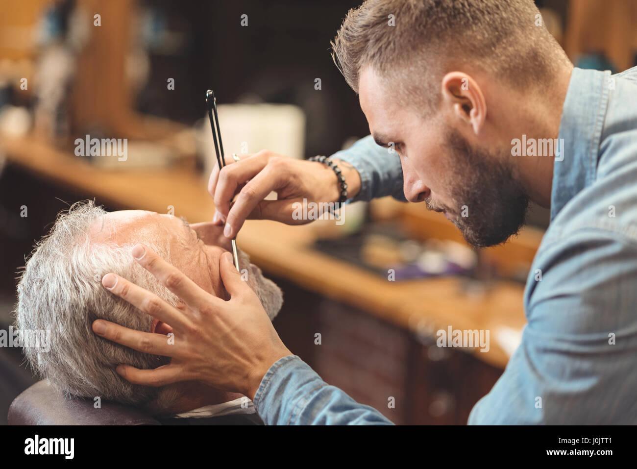 Junge Meister rasieren Bart des Clients im Frisörsalon Stockbild
