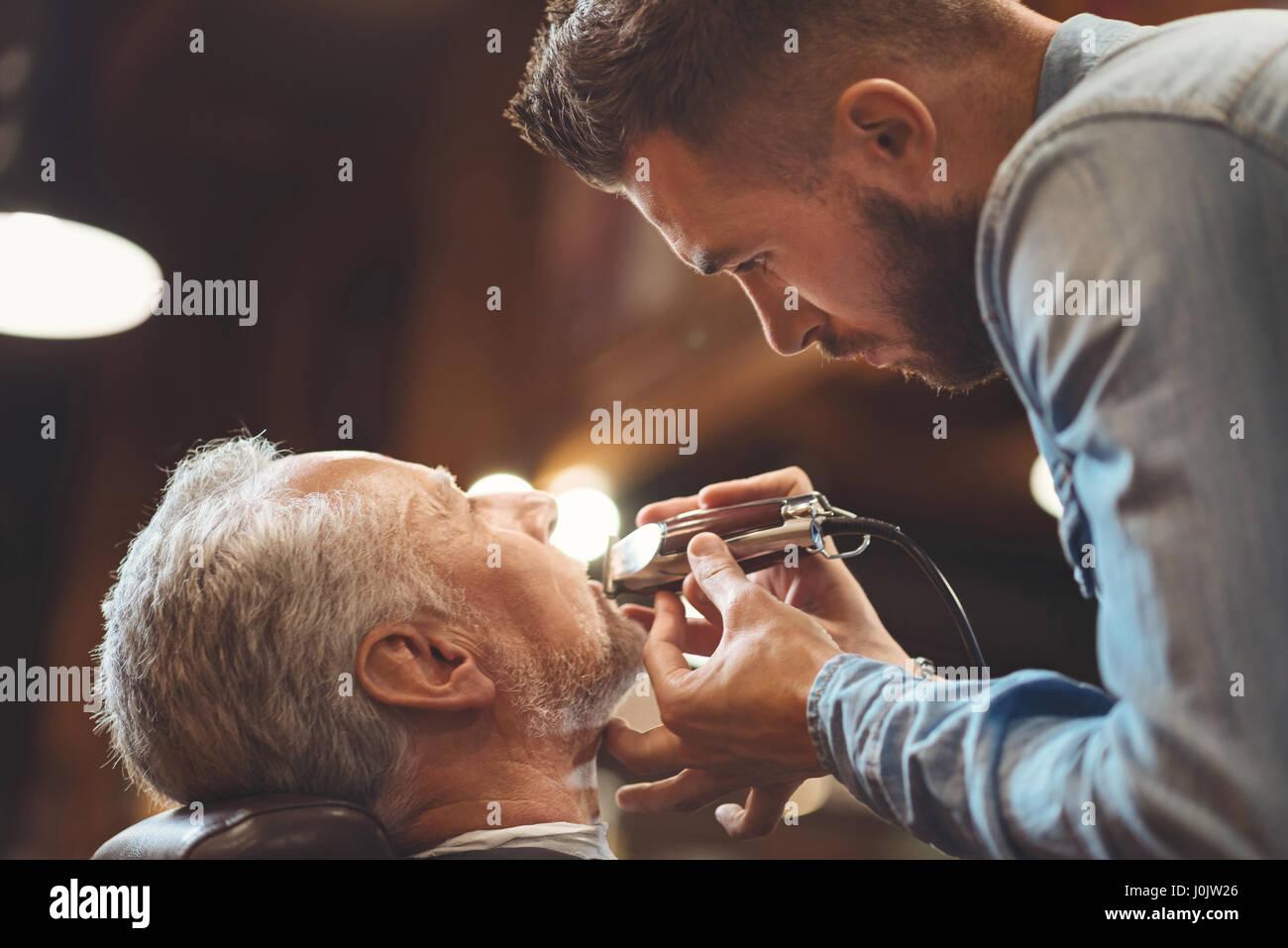 Emotionslos Friseur schneiden Bart des alten Clients im Frisörsalon Stockbild