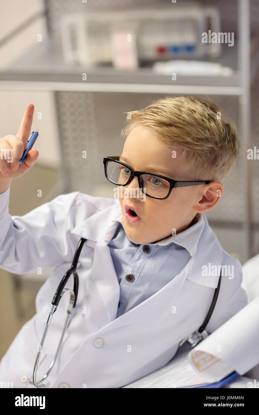 Kleiner Junge in Gläsern, die vorgibt, Arzt emotional gestikulierend Stockbild