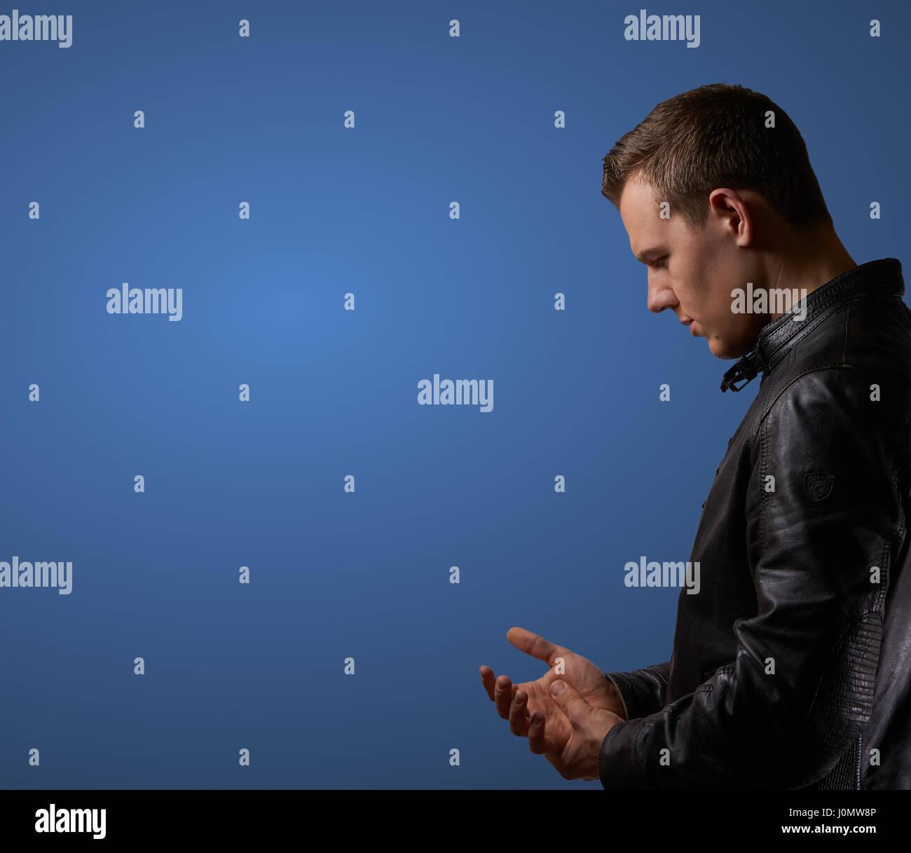 Profil von einem jungen Mann in Lederjacke, rieb seine Hand mit Exemplar erschossen Stockbild