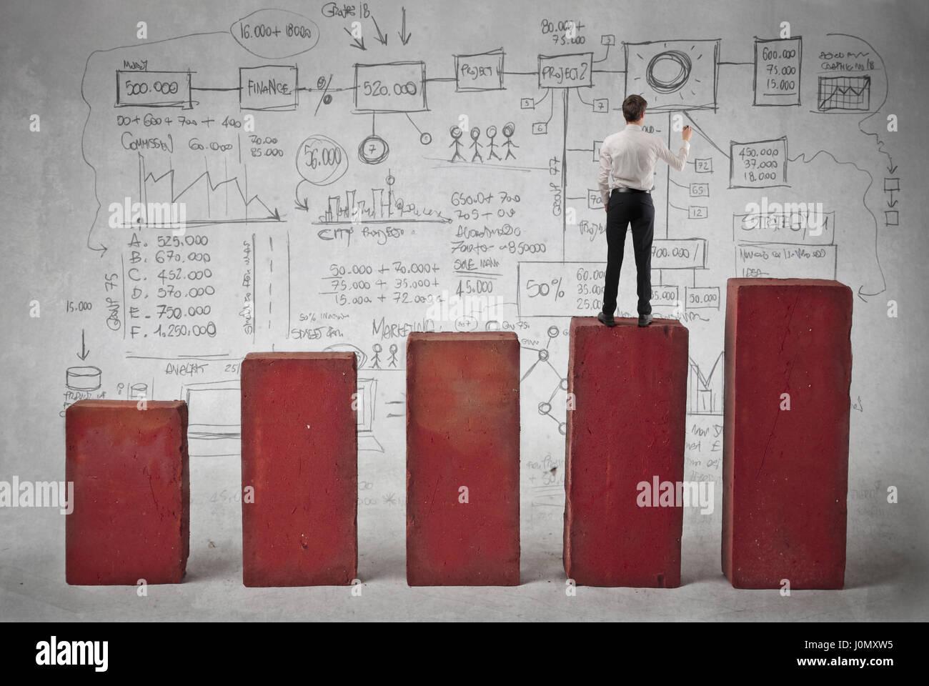 Geschäftsmann, stehend auf Statistik Stockbild
