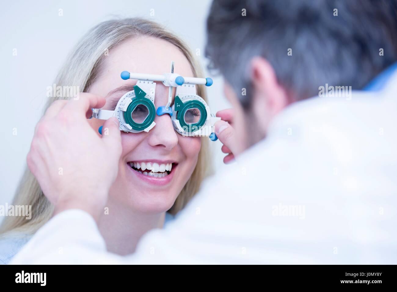 Optiker darstellende Auge test der jungen Frau. Stockfoto