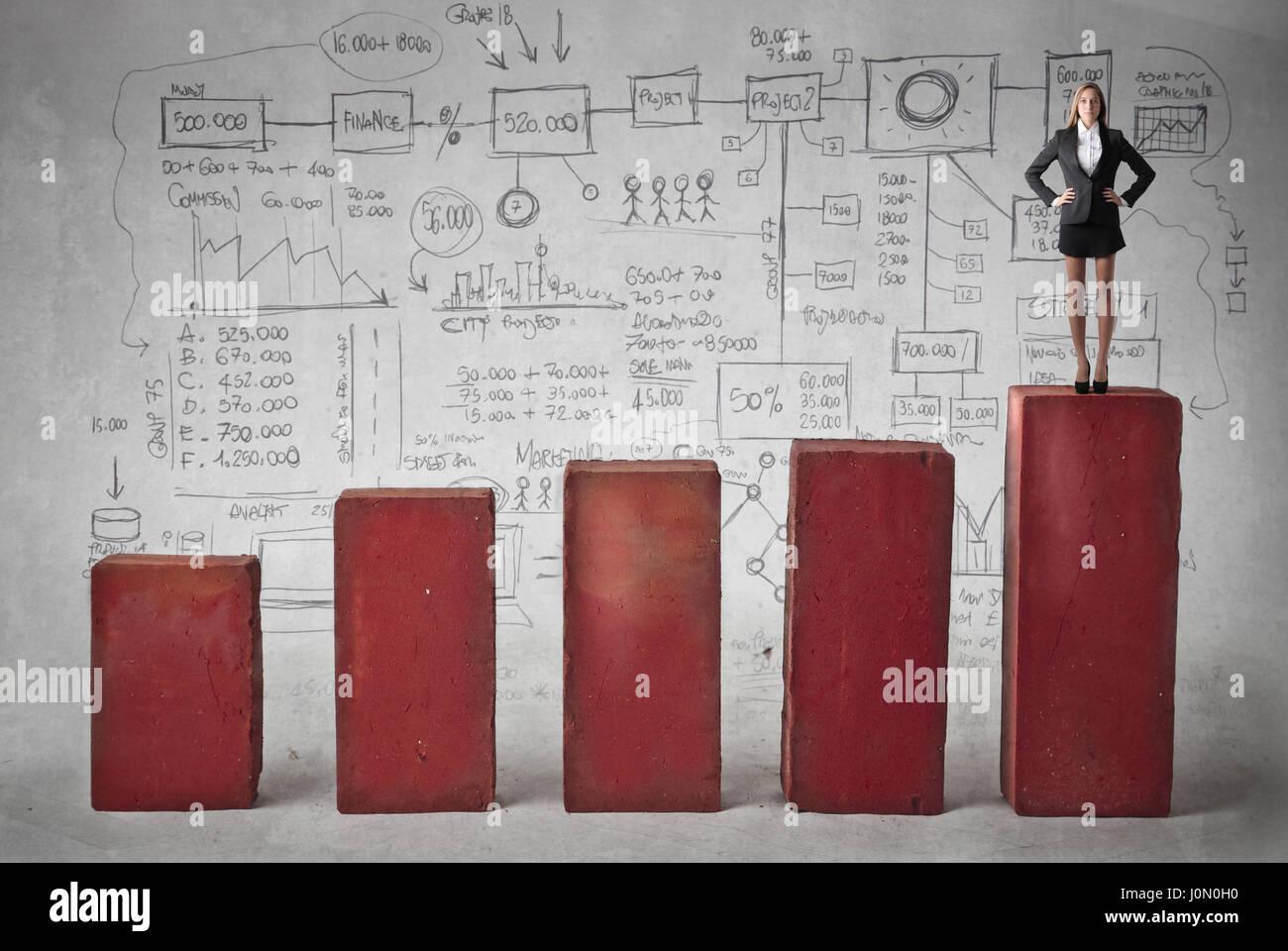 Geschäftsfrau, stehend auf Statistik Stockbild