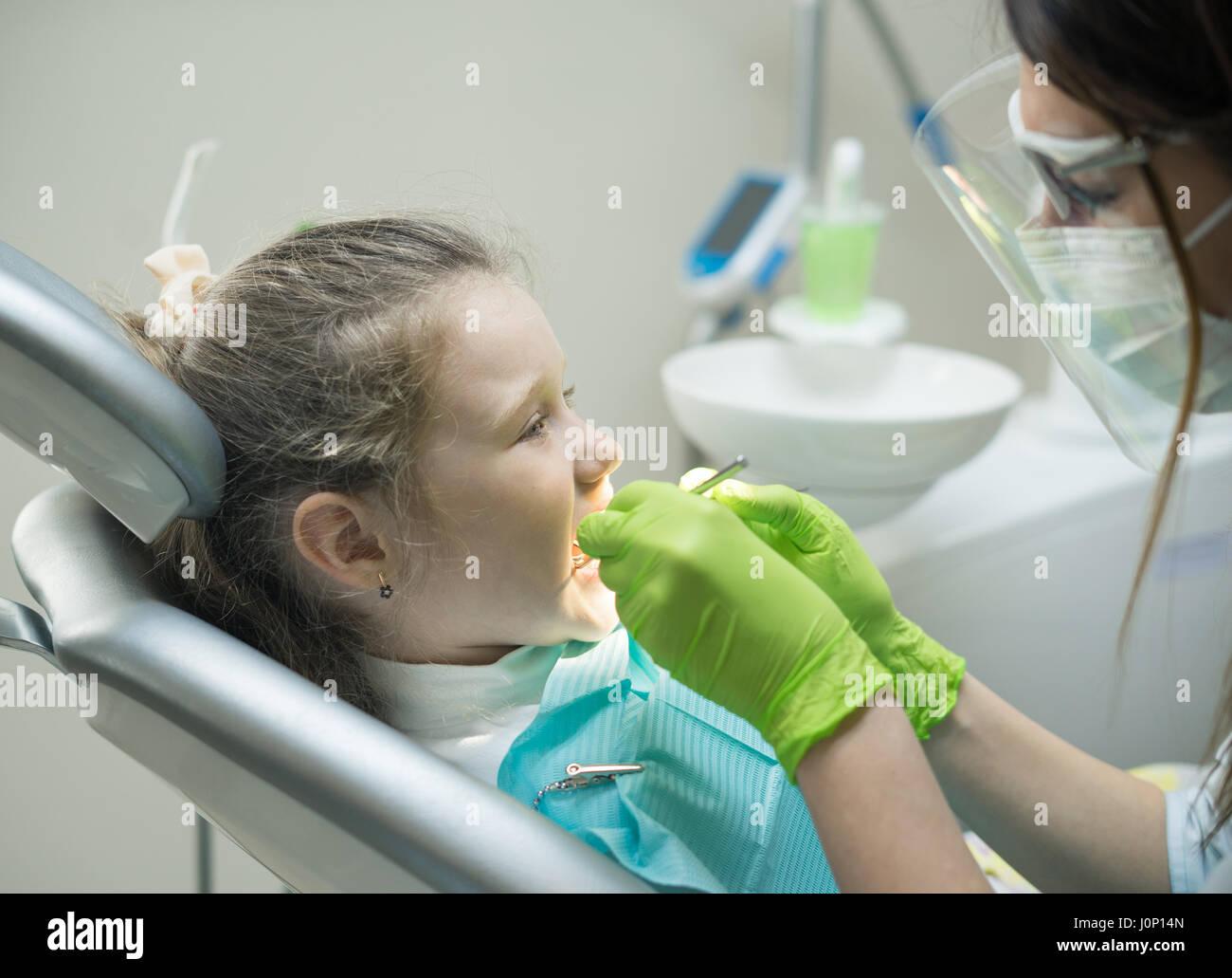Zahnärztin, die kleinen Mädchen Patienten überprüfen Stockbild