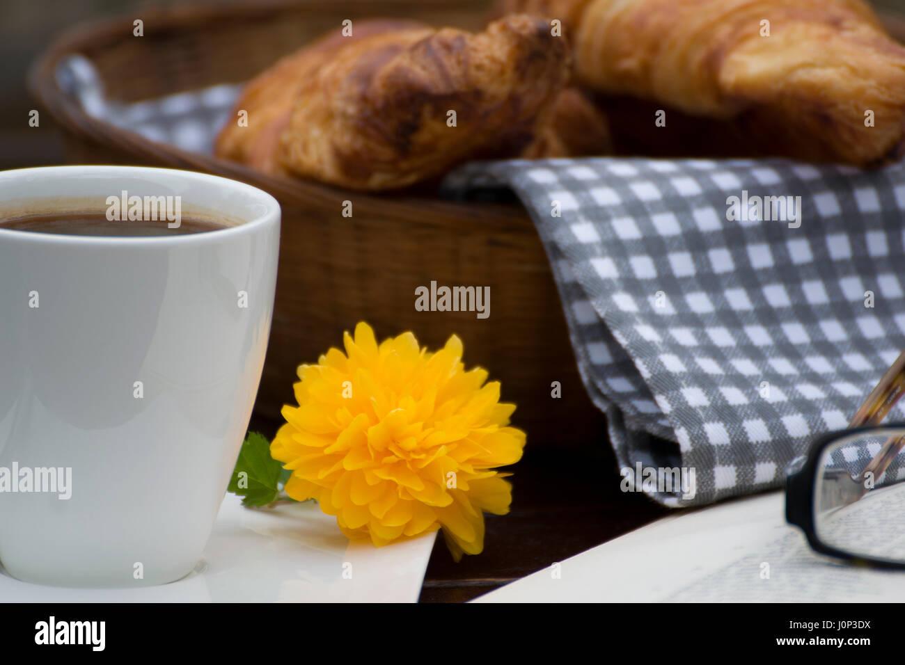 Nahaufnahme der einen Korb mit Croissants, eine Tasse Kaffee mit einem kleinen gelben Blume, ein offenes Buch und Stockfoto