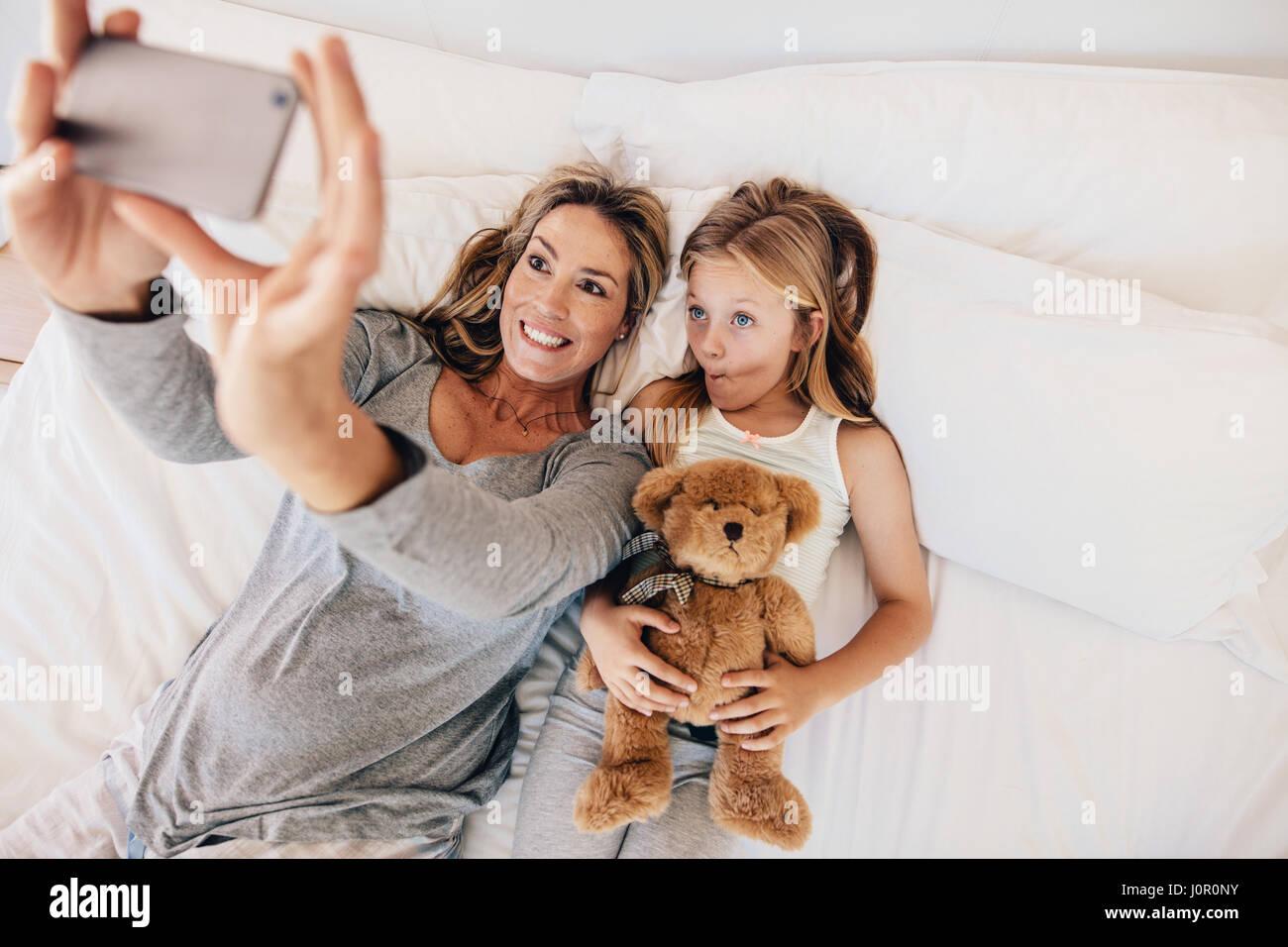 Mutter und Tochter am Bett liegen und unter Selbstbildnis mit Handy. Frau unter Selfie mit einem kleinen Mädchen Stockbild