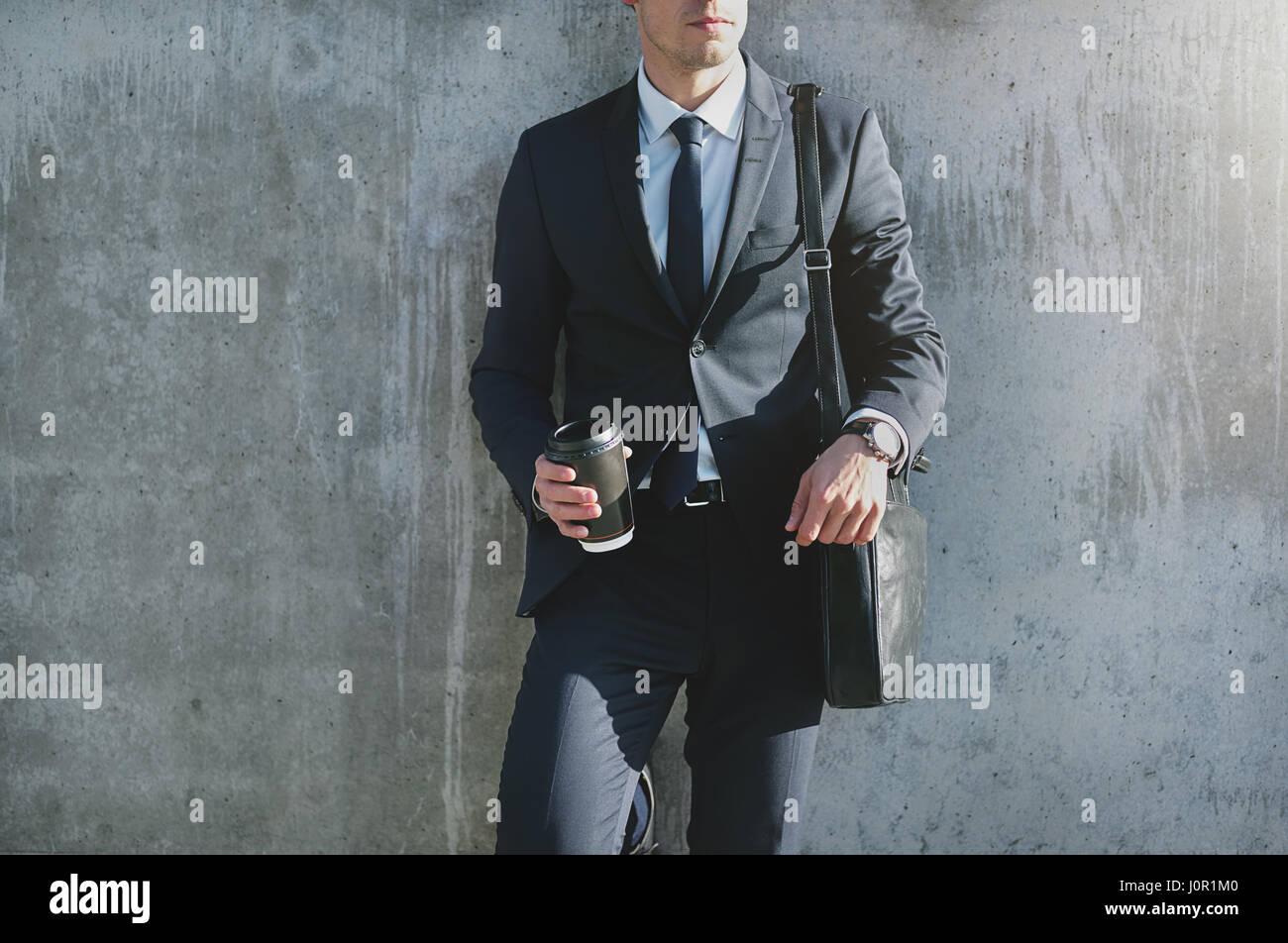 Stilvolle moderne Geschäftsmann stand an der grauen Wand und hält eine Tasse Kaffee. Stockbild
