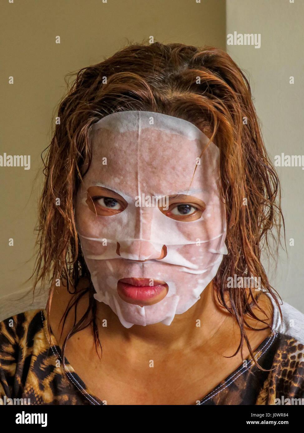 eine unglückliche asiatische Frau trägt eine Gesichtshaut Teint Maske. Stockbild