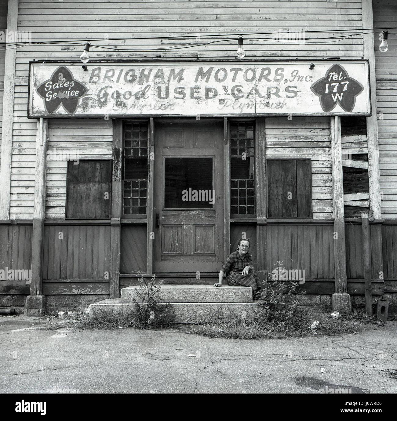 Eine alte Frau sitzt auf der Treppe ein verlassenes Autohaus in Marlboro, Massachusetts, USA. Stockbild