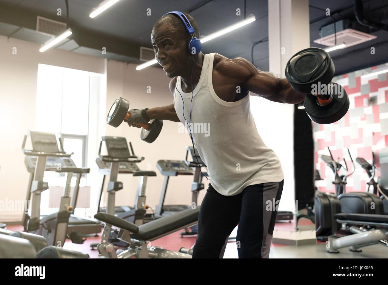 hartes Training. Muskulöse Schwarze Mann Übungen mit Hanteln für ...