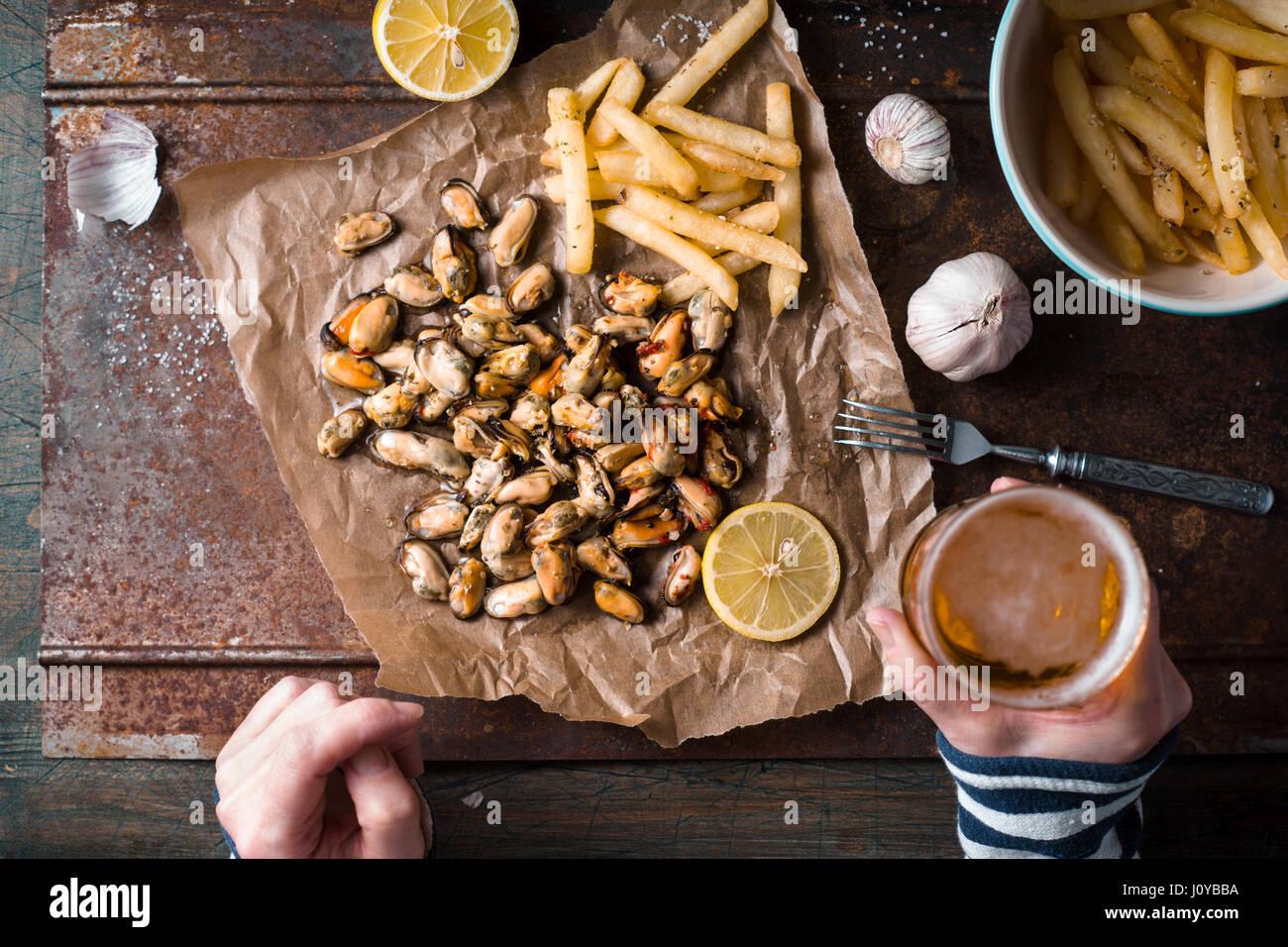 Biertrinken mit Muscheln und Pommes frites-Draufsicht Stockbild