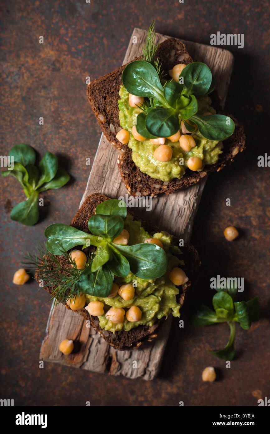 Open-Sandwich mit Avocado Creme und Grüns auf dem Metall Hintergrund vertikale Stockbild