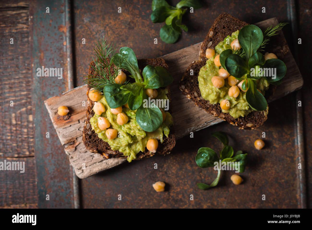 Open-Sandwich mit Avocado Creme und Grüns in der Draufsicht Metall Hintergrund Stockbild