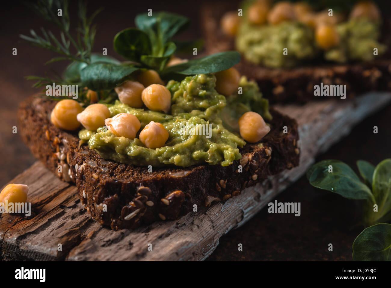 Open-Sandwich mit Avocado Creme und Grüns auf dem Holzbrett Stockbild
