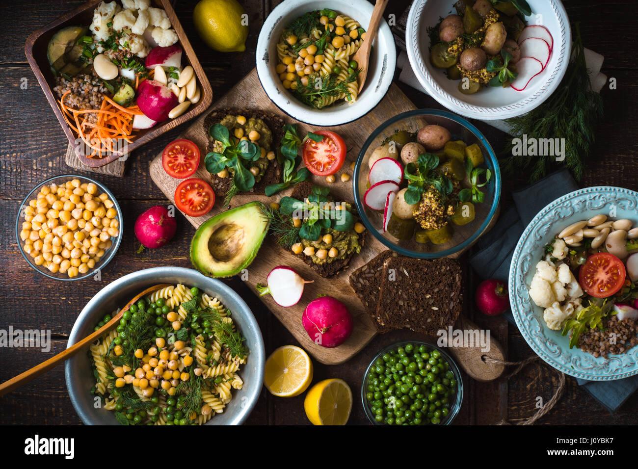 Verschiedene Salate und Snack auf der hölzernen Tischplatte anzeigen Stockbild