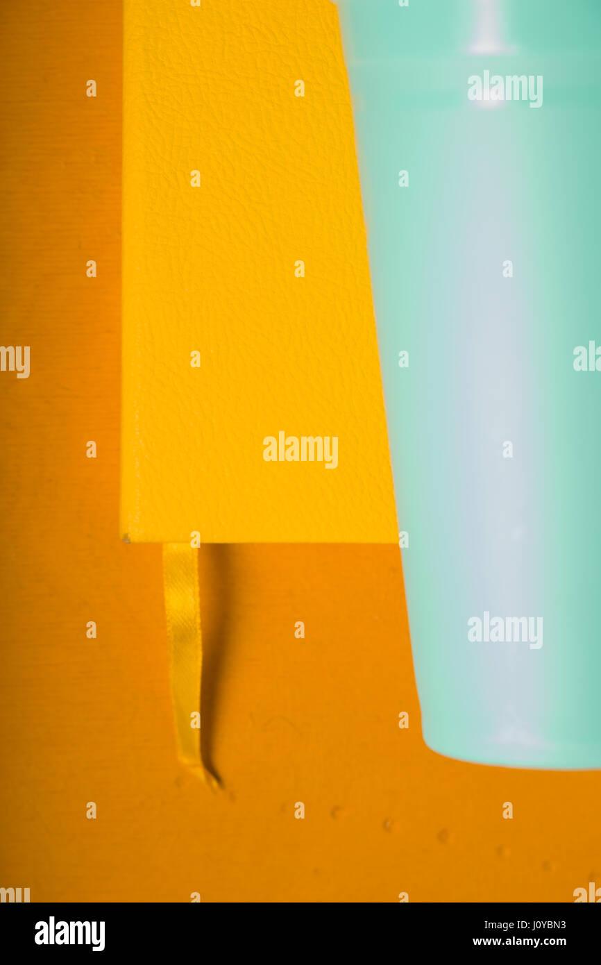 Gelben Notizblock und Türkis Kunststoffglas auf gelbem Hintergrund Stockbild