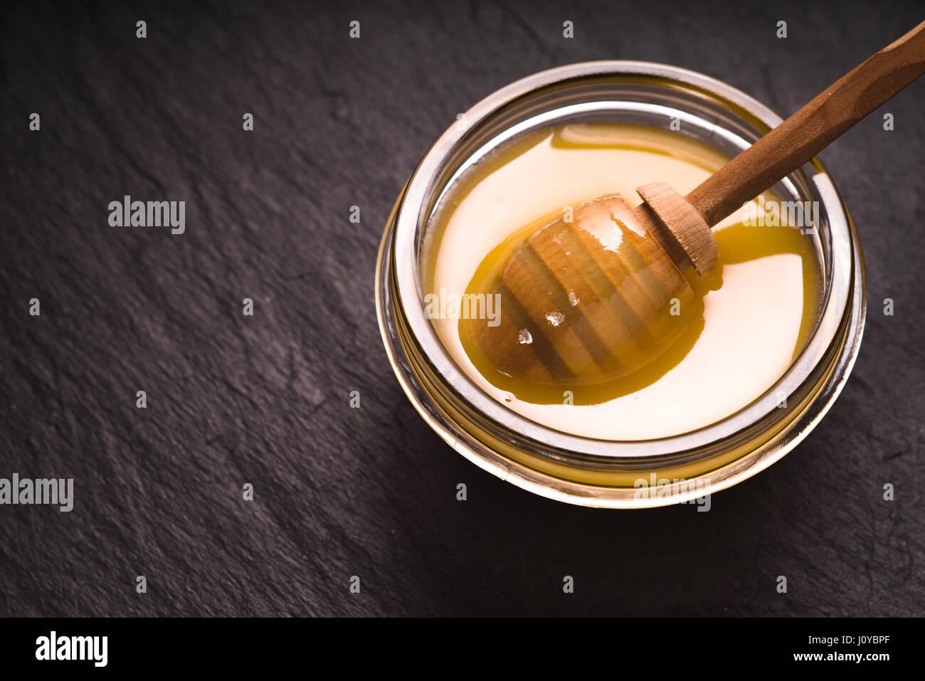 Löffel in eine Schüssel mit Honig auf einem dunklen Schiefer ...