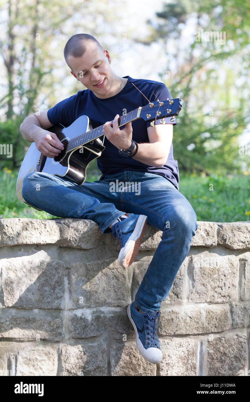 Hübscher junger Mann genießen den Park mit einer Gitarre. Tiefenschärfe und kleine Schärfentiefe. Stockbild