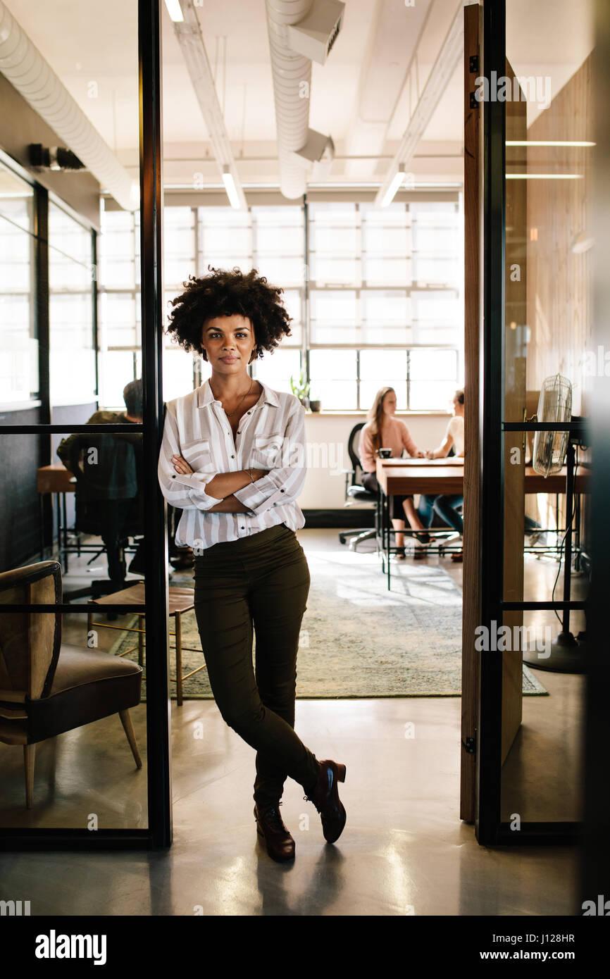 In voller Länge Portrait von selbstbewusste junge Frau in Tür des Büros mit ihren Armen stehe gekreuzt. Stockbild