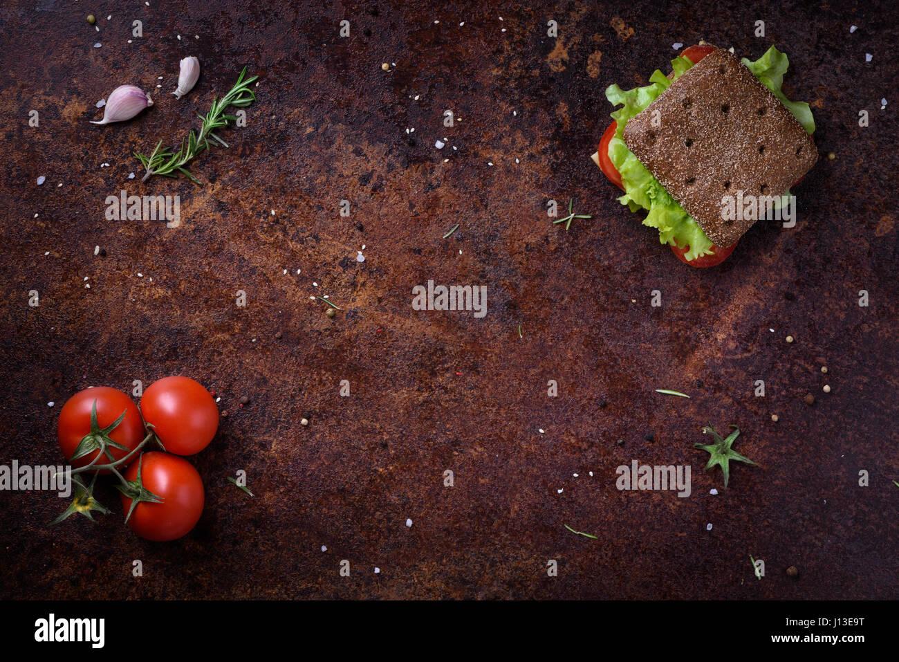 Vegetarisches Sandwich in Roggen-Brötchen mit Salat und Tomaten auf einem rustikalen Tisch oder Theke. Kopieren Stockbild