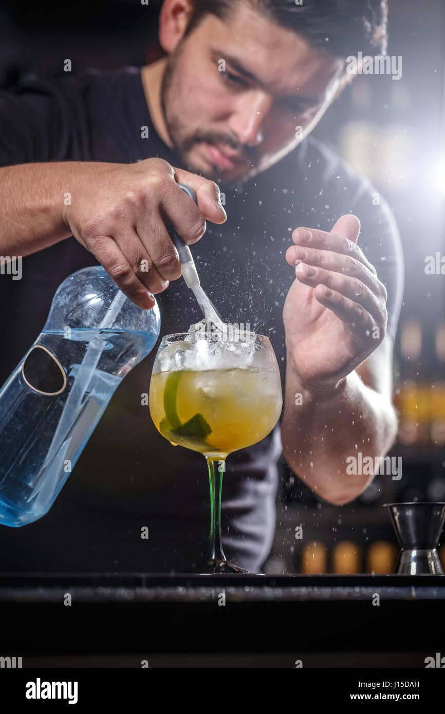 Barkeeper ist Soda Wasser gießen, er bereitet einen Mango-cocktail Stockbild