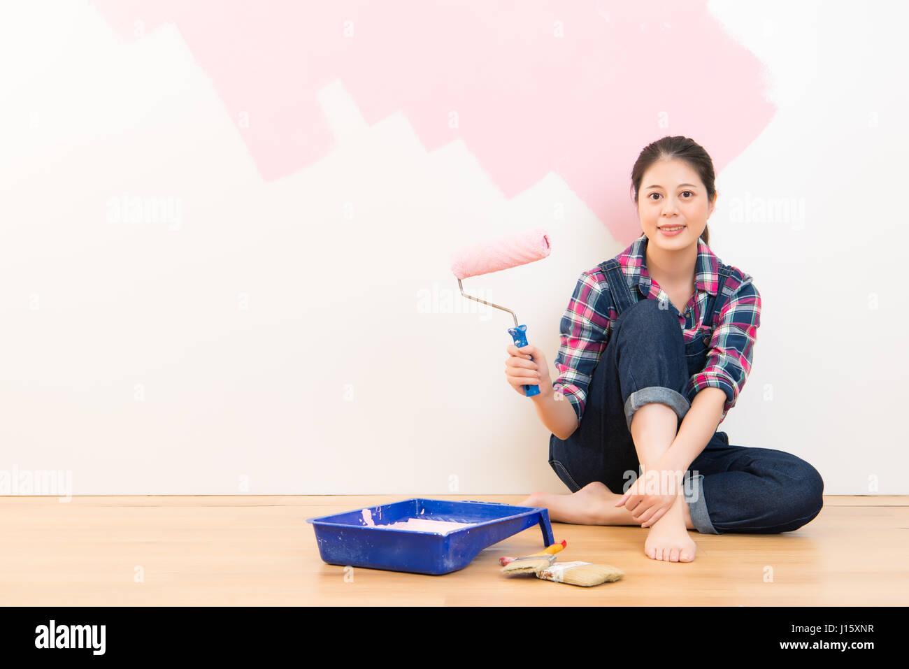 Frau Mit Walze Auftragen Rosa Farbe An Der Wand. Multiethnische Asiatin  Modell